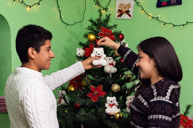 Młoda para wspólnie dekoruje choinkę w domu dziadków