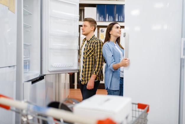 Młoda para wybiera lodówkę w sklepie