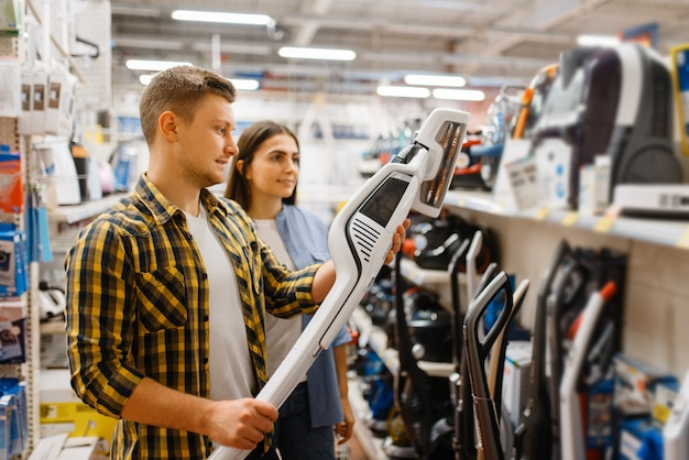 Młoda para wybiera odkurzacz w sklepie elektronicznym. mężczyzna i kobieta kupują domowe urządzenia elektryczne na rynku