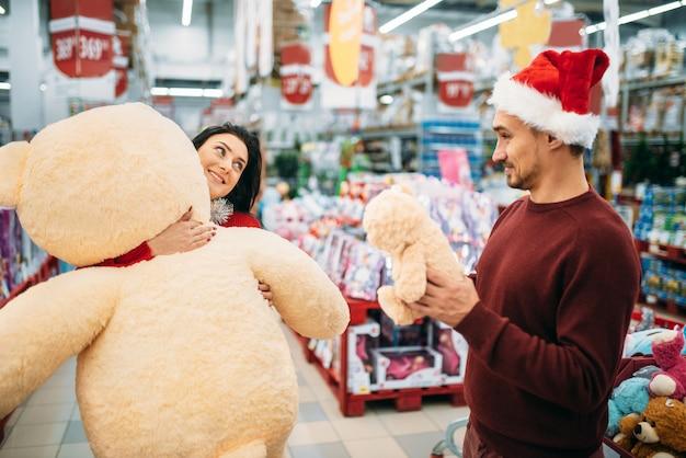 Młoda para wybiera pluszowe zabawki na boże narodzenie w supermarkecie, rodzinna tradycja. grudniowe zakupy noworocznych artykułów świątecznych i dekoracji