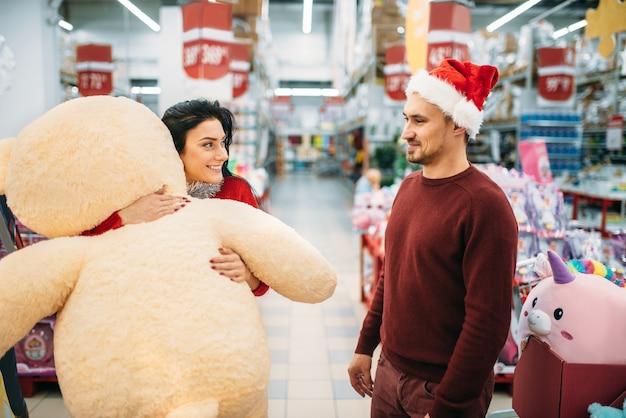 Młoda para wybiera pluszowe zabawki w supermarkecie