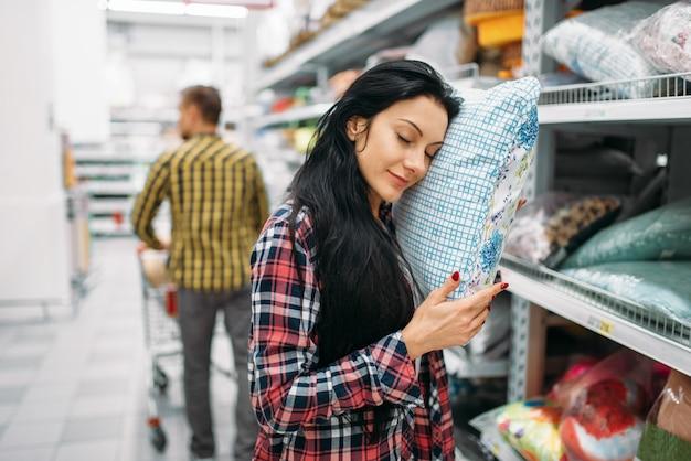 Młoda para wybiera poduszkę w supermarkecie. klienci płci męskiej i żeńskiej na rodzinne zakupy. mężczyzna i kobieta kupują towary do domu