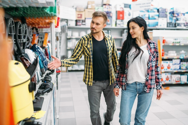 Młoda para wybiera sprzęt gospodarstwa domowego w supermarkecie. klienci płci męskiej i żeńskiej na rodzinne zakupy. mężczyzna i kobieta kupują towary do domu