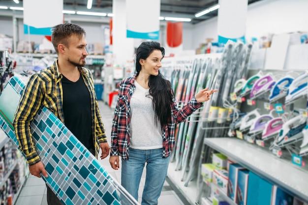 Młoda para wybiera żelazko elektryczne w supermarkecie. klienci płci męskiej i żeńskiej na rodzinne zakupy. mężczyzna i kobieta kupują towary do domu