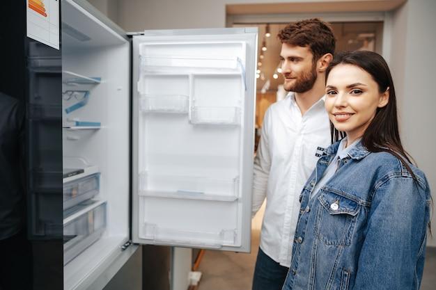 Młoda para wybierając nową lodówkę w sklepie agd