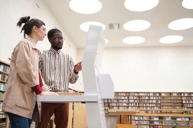 Młoda para wybierająca książki na specjalnym sprzęcie stojąc w bibliotece