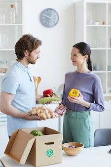 Młoda para wyjmuje świeże warzywa z pudełka i rozmawia ze sobą, stojąc w kuchni