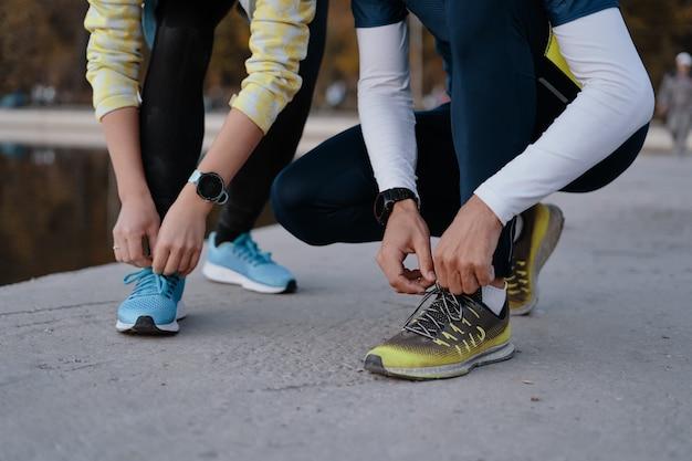 Młoda para yying buty sportowe.