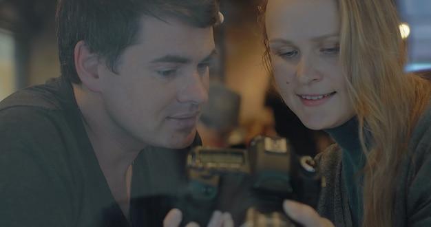 Młoda para z aparatem wybiera najlepsze ujęcia