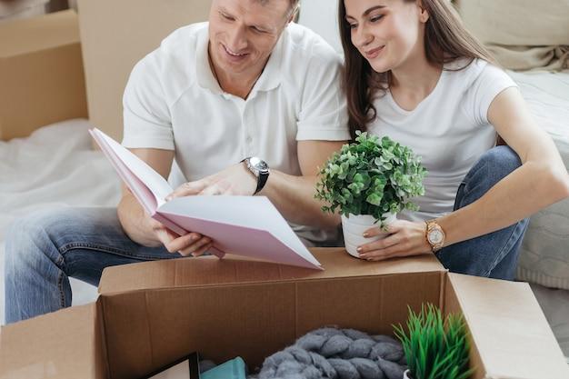 Młoda para z bliska szuka rodzinnego zdjęcia w nowym mieszkaniu