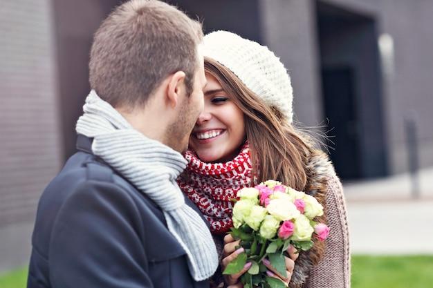 Młoda para z kwiatami całuje się w mieście