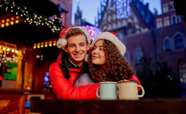 Młoda para z napojami na jarmarku bożonarodzeniowym we wrocławiu