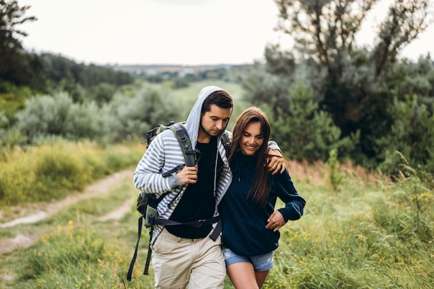 Młoda para z plecakami na plecach w lesie. kochający mężczyzna całuje swoją piękną dziewczynę podczas wędrówki po lesie