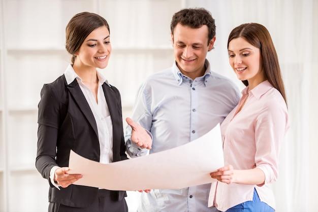 Młoda para z pośrednikiem handlu nieruchomościami ogląda plan domu.