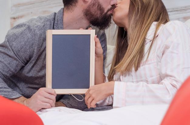 Młoda para z ramą pocałunki na łóżku
