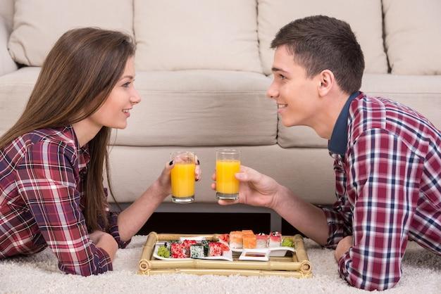 Młoda para z sushi i napoje na podłodze w domu.