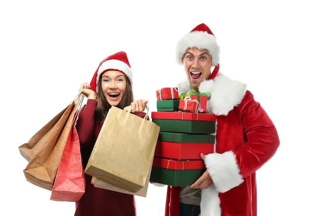 Młoda para z zakupami świątecznymi na białym tle