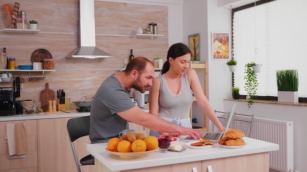 Młoda para za pomocą laptopa w kuchni. szczęśliwy żonaty mąż i żona w piżamie, korzystający z nowoczesnych technologii internetowych online, uśmiechnięty i szczęśliwy rano. czytanie wiadomości przeglądanie internetu