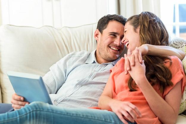 Młoda para zabawy podczas korzystania z cyfrowego tabletu na kanapie w salonie