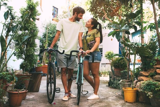 Młoda para zakochana jeżdżąca na rowerach ulicą pełną roślin i kwiatów lifestyle