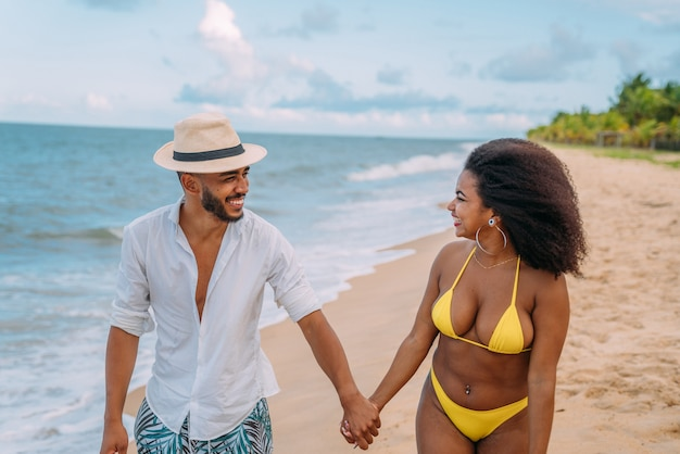 Młoda para zakochana na plaży, wakacje, szczęśliwy i uśmiechnięty trzymając się za ręce