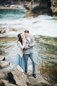 Młoda para zakochana nad górską rzeką w karpatach
