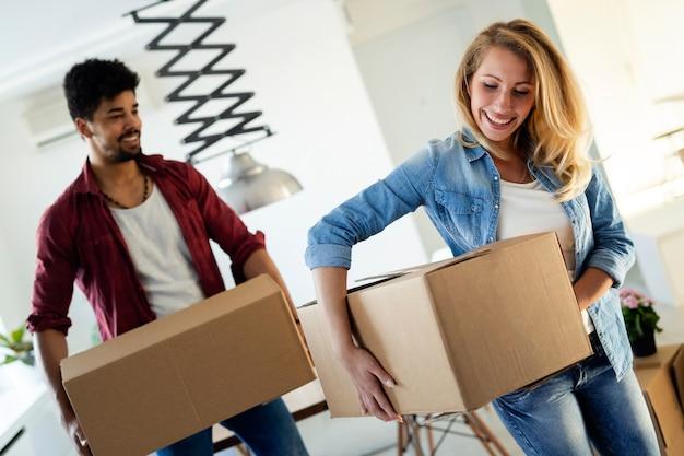 Młoda para zakochana rozpakowująca kartony w nowym domu porusza się w koncepcji