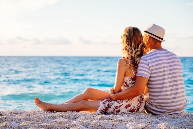 Młoda para zakochana siedzi na plaży nad morzem, ciesząc się romantyczny wieczór i oglądając zachód słońca. latem rodzina wypoczywa na plaży.