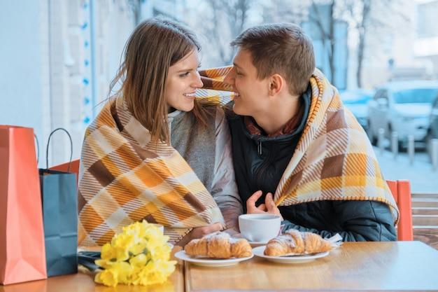 Młoda para zakochana w kawiarni na świeżym powietrzu pod szkocką kratą