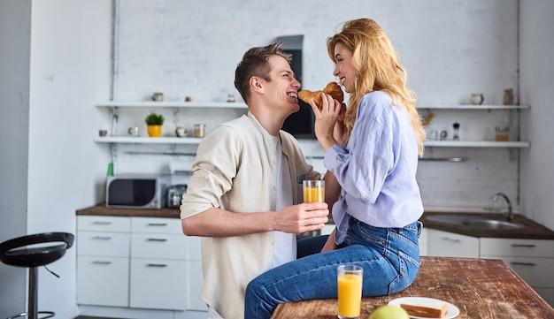 Młoda para zakochana w kuchni karmi się rogalikiem. romantyczne śniadanie.
