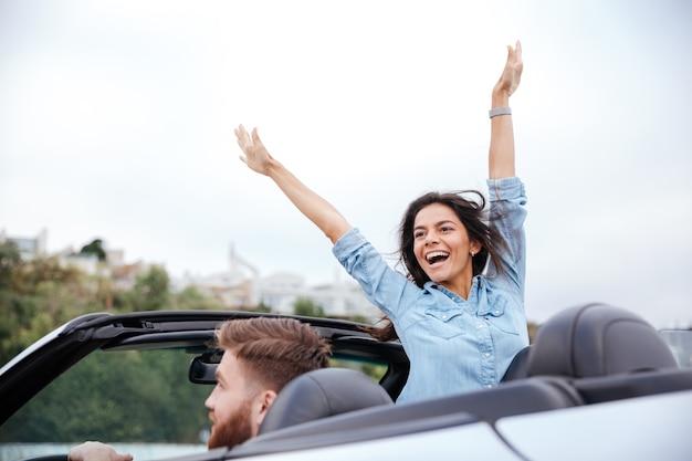 Młoda para zakochana w podróży samochodem w kabriolecie