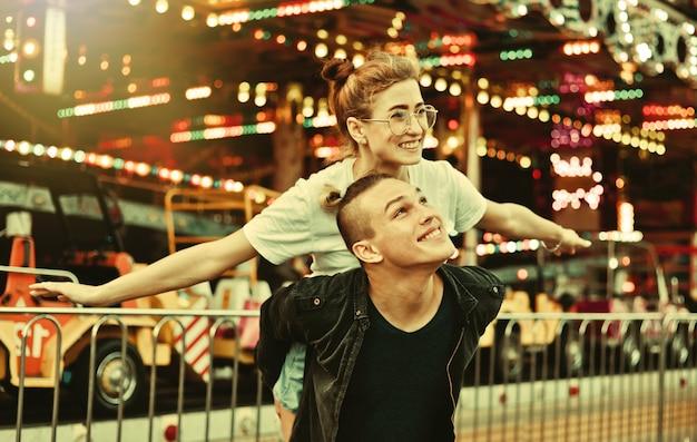 Młoda para zakochana wspólna zabawa w parku rozrywki koncepcja wakacji, miłości i przyjaźni