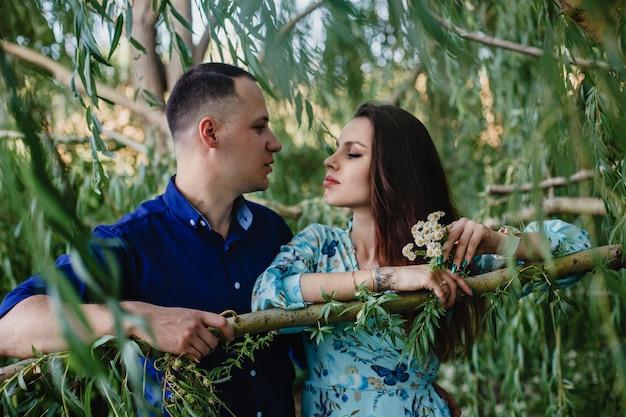 Młoda para zakochana wśród gałązek wierzby latem w ogrodzie