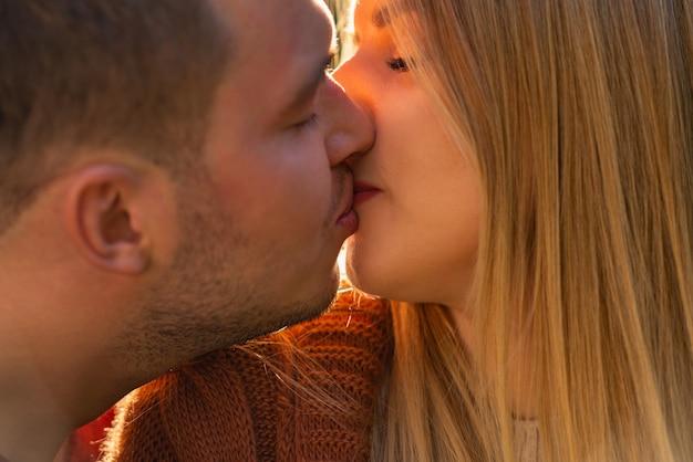Młoda para zakochanych, ciesząc się romantycznym pocałunkiem z bliska przyciętego widoku ich twarzy w profilu