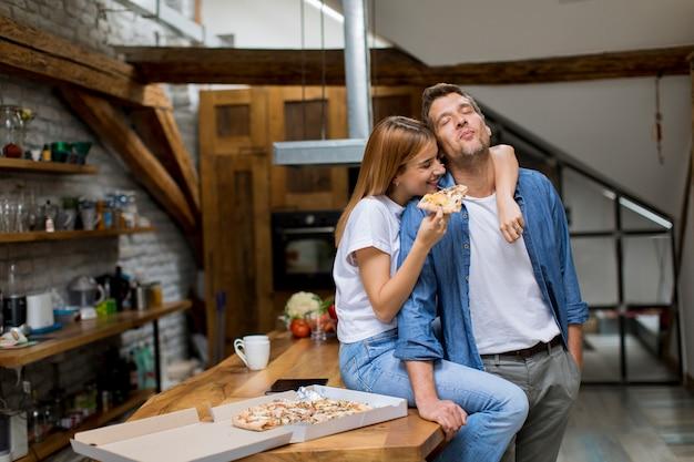 Młoda para zakochanych jeść pizzę w rustykalnym domu
