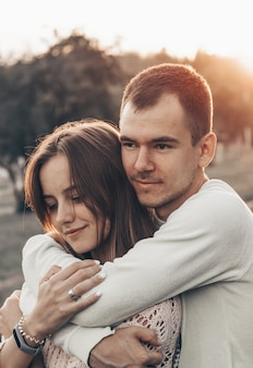 Młoda para zakochanych na świeżym powietrzu. uśmiechają się i patrzą na siebie. bliska romantyczny portret piękna szczęśliwa para zakochanych przytula i zabawy, wieczorne światło słoneczne, słoneczne kolory, styl vintage.