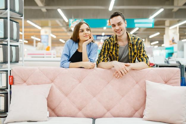 Młoda para zakochanych pozuje na różowej kanapie w sklepie meblowym.