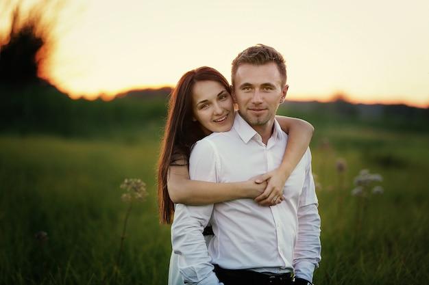 Młoda para zakochanych przytulanie na zewnątrz w polu o zachodzie słońca w letni dzień. koncepcja romantyczna, miłość, ludzie. historia miłosna