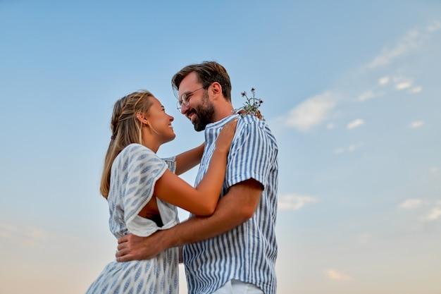Młoda para zakochanych ściska się nad błękitnym niebem, romantycznie spędzając czas ciesząc się sobą i wakacjami.