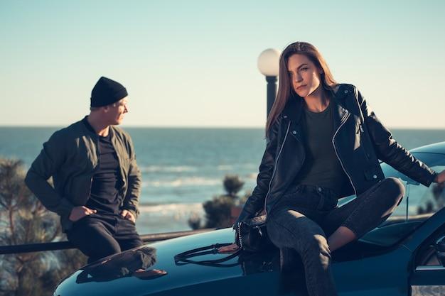 Młoda para zakochanych spacery nad morzem. wiosna jesień. facet ma na sobie kurtkę i kapelusz. dziewczyna w kapeluszu i skórzanej kurtce z szalikiem