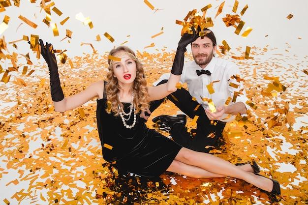 Młoda para zakochanych stylowe, siedząc na podłodze, rzucając złotym konfetti