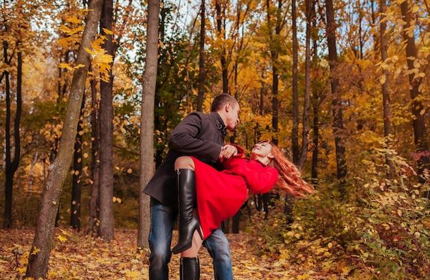 Młoda para zakochanych tańczy w jesiennym lesie wśród kolorowych drzew