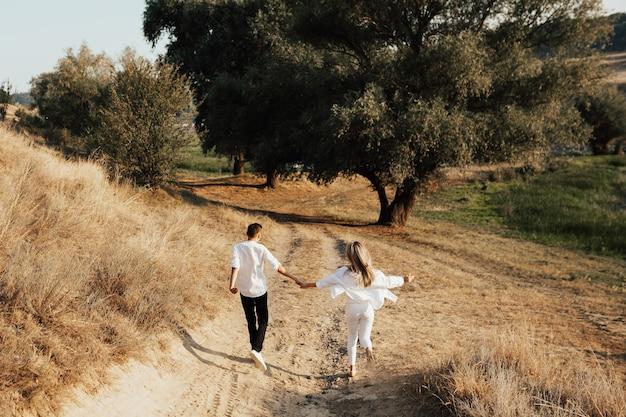 Młoda para zakochanych trzyma się za ręce, biegając, bawiąc się i podziwiając piękną przyrodę w parku.