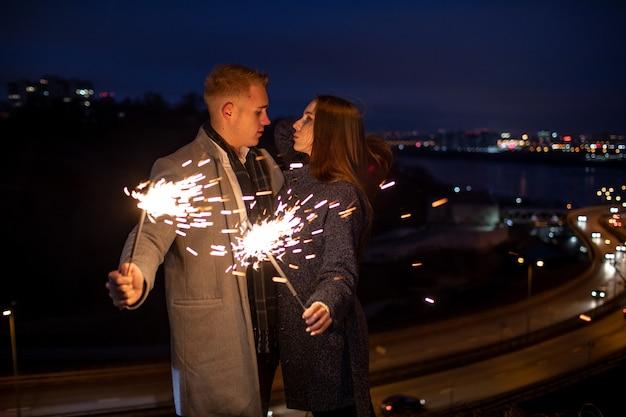 Młoda para zakochanych trzymać w rękach sparklers