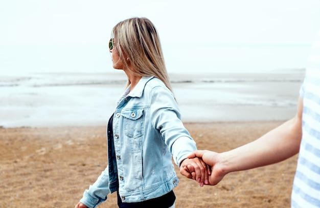 Młoda para zakochanych trzymając się za ręce spacerują plażą przed brzegiem morza we mgle. szczęśliwa młoda rodzina. koncepcja podróży i wakacji.