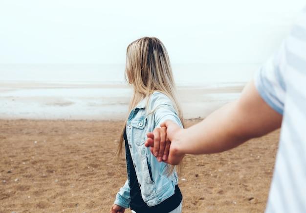 Młoda para zakochanych, trzymając się za ręce, spaceruje przy plaży nad morzem we mgle