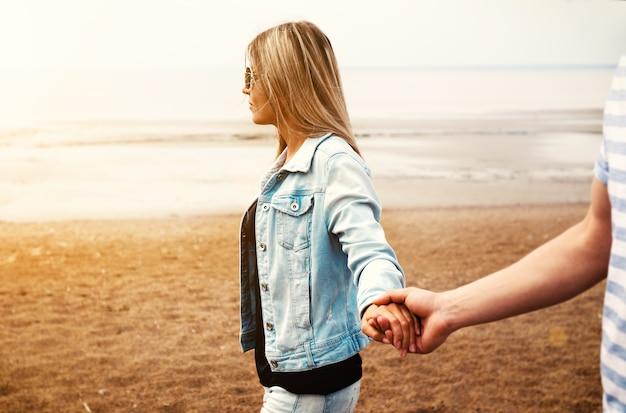 Młoda para zakochanych, trzymając się za ręce, spaceruje przy plaży przed zachodem słońca latem