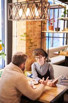 Młoda para zakochanych z touchpadem, rozmawiając o wideo online, siedząc w luksusowej kawiarni lub restauracji