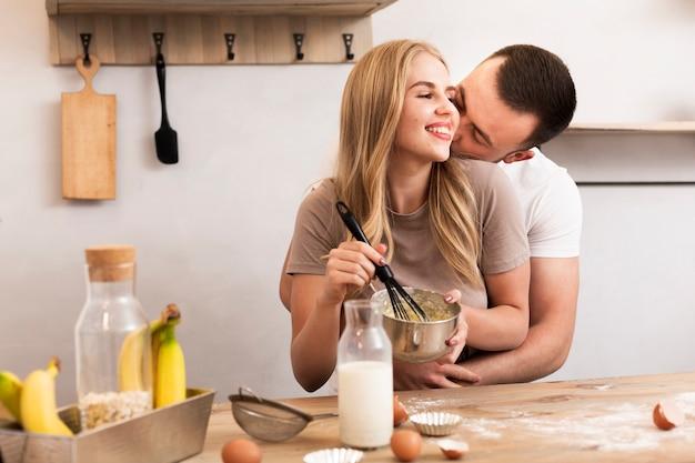 Młoda para zamieszać jajka i mleko w misce