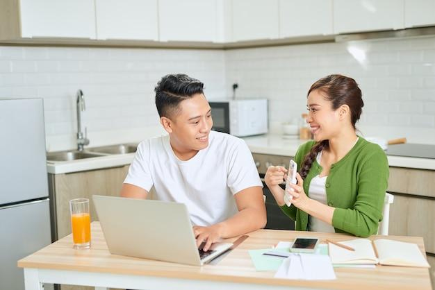 Młoda para zarządzająca finansami, przeglądająca swoje rachunki bankowe przy użyciu komputera przenośnego i kalkulatora w nowoczesnej kuchni.